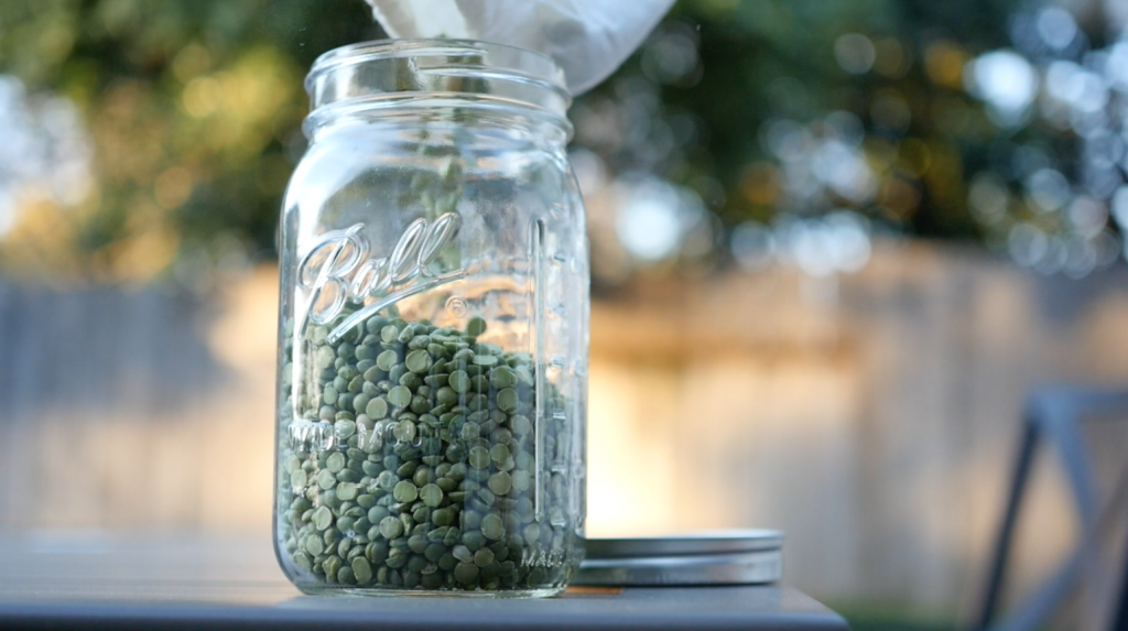 Green lentils being poured into a glass Ball Mason jar