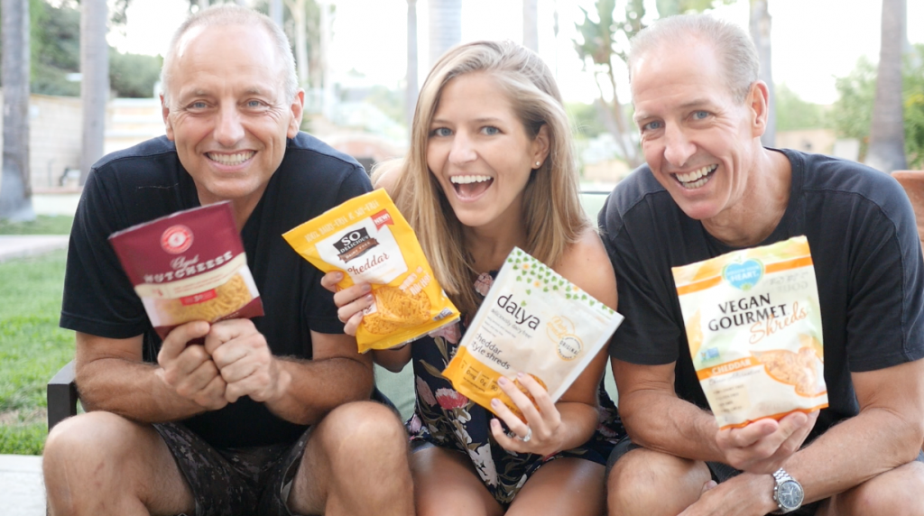 Greg Hicks, Michelle Cehn, and Dan Safko hold up four bags of vegan shredded cheddar cheese