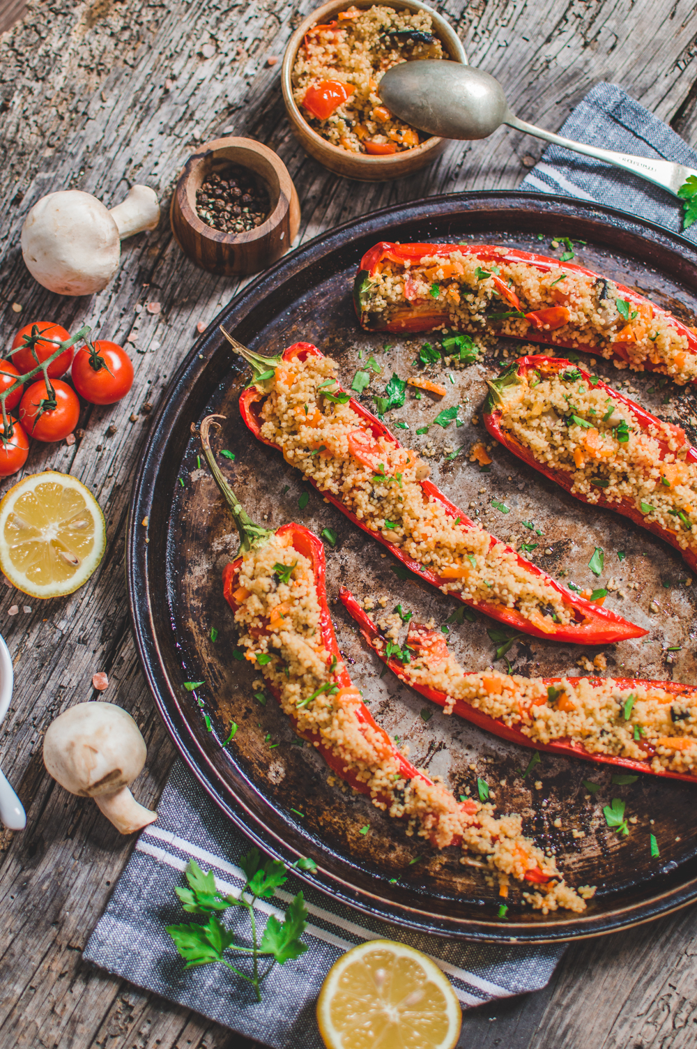 Couscous Stuffed Peppers served on a round serving dish with some ingredients on the side
