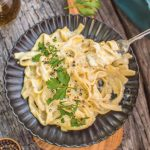 Creamy Vegan Fettuccine Alfredo Served on a Dark Grey Dish