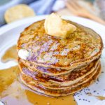 Vegan Lemon Poppyseed Pancakes Stacked with Syrup and Butter